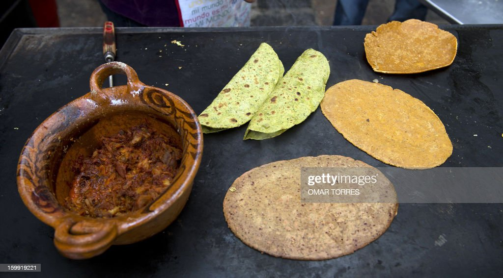 Veronica Mendoza cooks Mexican tortillas made with spinach and wheat bran (green), beet and amaranth (pink) and chick-pea and chili (ochre) in her restaurant in Mexico City on January 22, 2013. Her take on the traditional tortillas, made with vegetables and grains, are an attempt to make 'quesadillas' (stuffed fried tortilla) healthier.