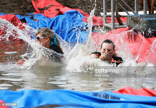 Veronica Salka left and friend Sidney Brega both from Bayfield Colorado take the plunge jumping off a swing at MuckFest MS Denver July 15 2017 at...