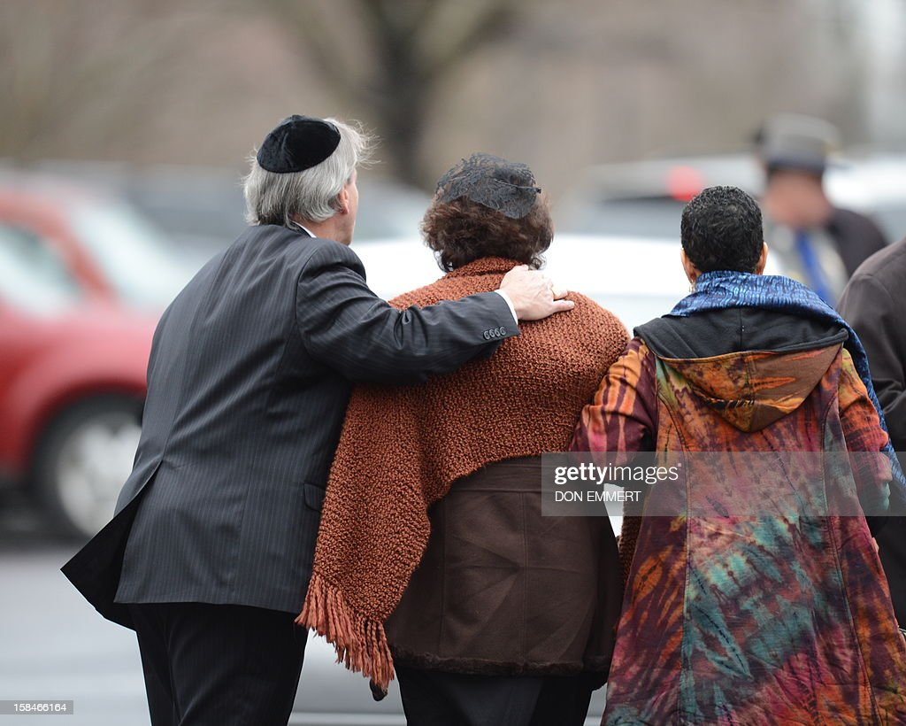 Veronika Pozner(C), mother of Noah Pozner, arrives for her son's funeral December 17, 2012 at the Abraham L. Green and Son Funeral Home in Fairfield, Connecticut. Funerals began Monday after the school massacre that took the lives of 20 small children and six staff, triggering new momentum for a change to America's gun culture. The first burials, held under raw, wet skies, were for two six-year-old boys who were among those shot in Sandy Hook Elementary School. On Tuesday, the first of the girls, also aged six, was due to be laid to rest. There were no Monday classes at all across Newtown, and the blood-soaked elementary school was to remain a closed crime scene indefinitely, authorities said. AFP PHOTO/Don Emmert