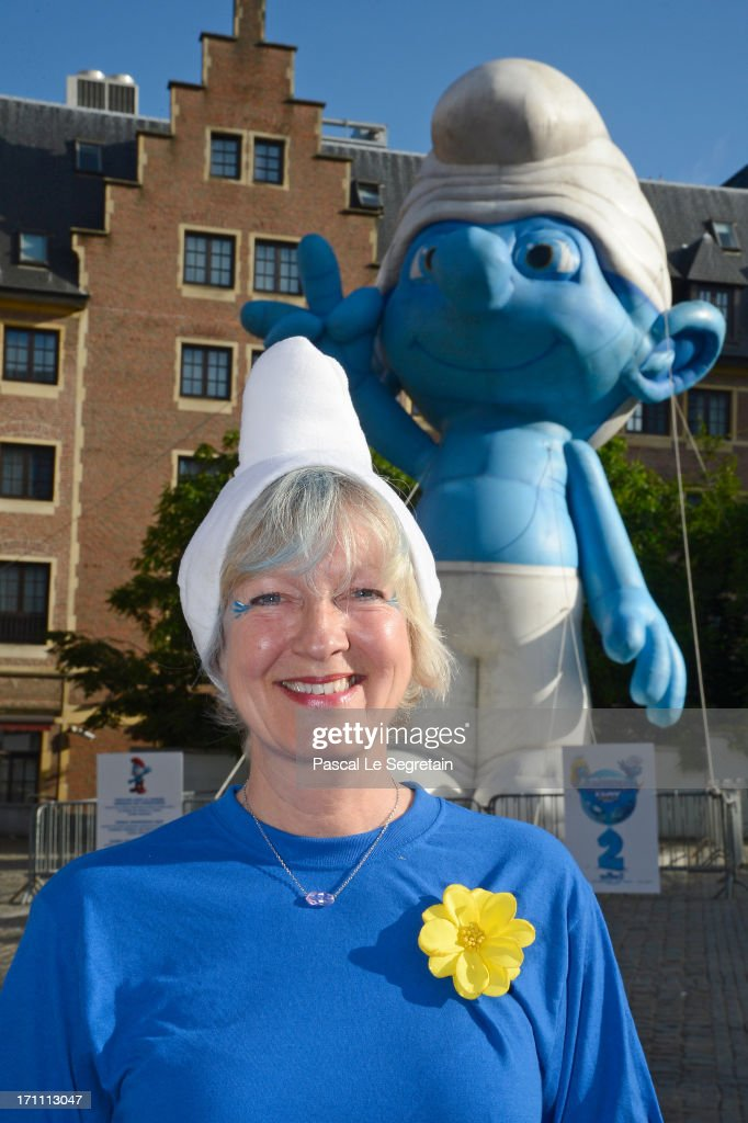 Veronique Culliford, the daughter of cartoonist Peyo, the creator of The Smurfs, Peyo, poses by a giant Smurf character during Global Smurfs Day celebrations on June 22, 2013 in Brussels, Belgium.