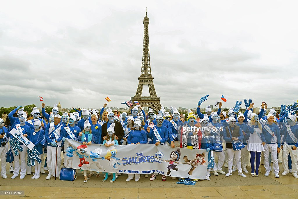 Veronique Culliford, the daughter of late cartoonist Peyo, the creator of The Smurfs, and producer Jordan Kerner, and Smurf Ambassadors pose for a group photo on the Trocadero plaza as part of Global Smurfs Day celebrations on June 22, 2013 in Paris, France. The Eiffel tower is seen behind.