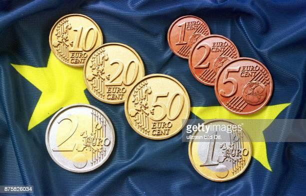 Verschiedene Euro Münzen 1 Euro 2 Euro und die Euro Cent Münzen liegen auf einer Europa Fahne 1998