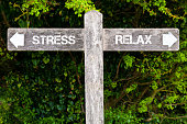 Wooden signpost with two opposite arrows over green leaves background. STRESS versus RELAX directional signs, Choice concept image