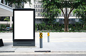 Vertical blank  billboard at bus stop outdoor advertise on street Mock up. The poster on the road with motion moving bus