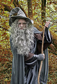 Vertical image of a mature wizard in a forest in autumn