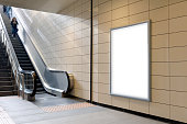 Vertical light box poster mockup in metro station, high resolution.