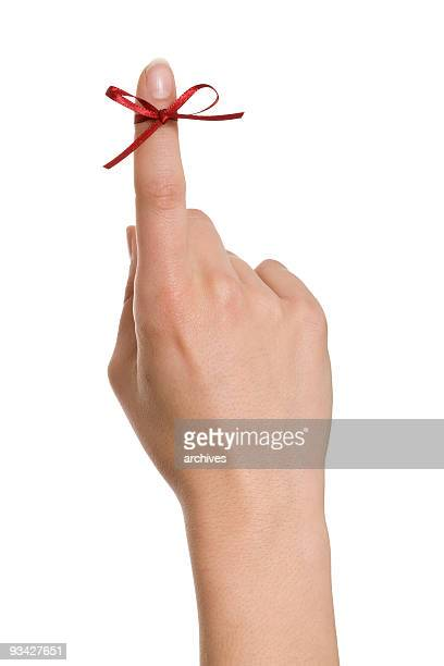 Vertical shot of a hand with a red string tied to finger