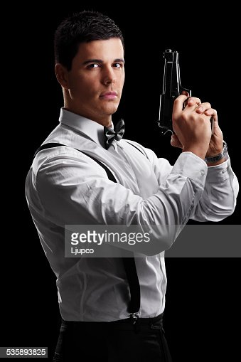 Vertical shot of an elegant man holding a gun : Stock Photo