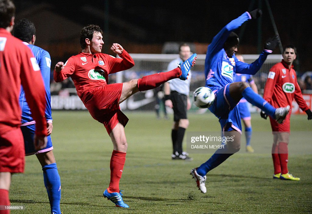 Vertou's player Lionel Cottereau (L) kicks the ball past Evian's player Sidney Govou (R) during the French Cup football match between Vertou and Evian on January 22, 2013, at the Echalonnieres stadium in Vertou, western France. AFP PHOTO / DAMIEN MEYER