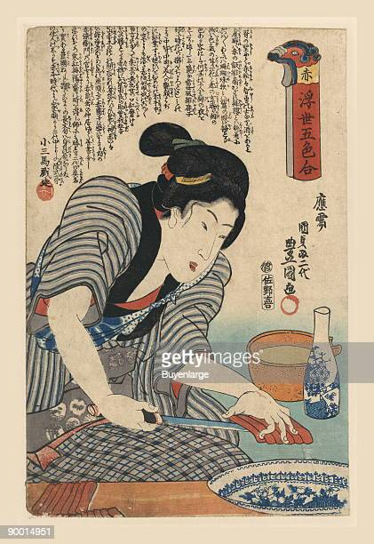 Very carefuly and with a very sharp blade this Japanese woman prepares sashimi for the family A sake japanese rice wine sits next to a pot ready to...