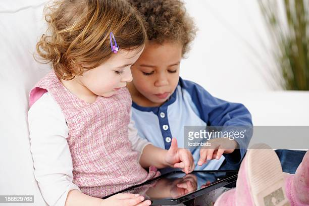 Very Cute Pair Of Toddlers Using Digital Tablet