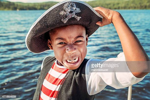Very expressive african-american child dressed as pirate on a lake.