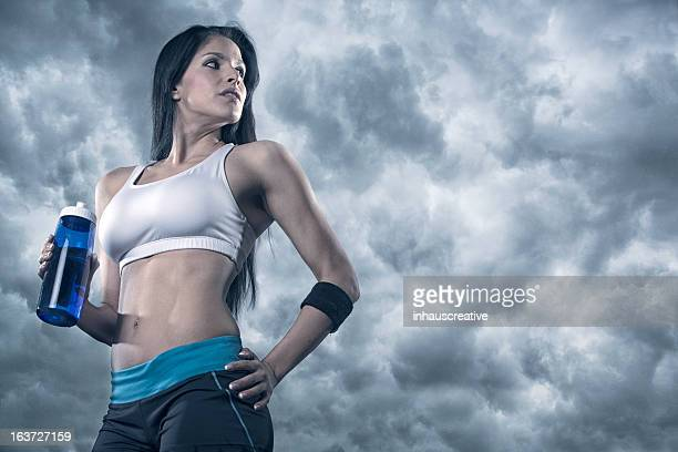 Very Fit Woman Holding a water bottle on cloudy background