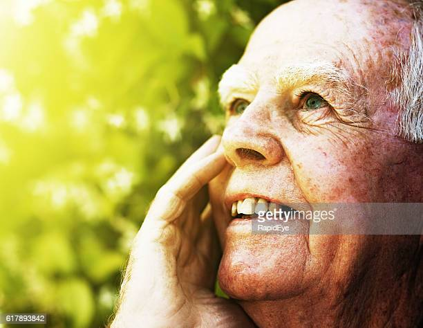 Very old man in garden looks up, smiling, hand raised