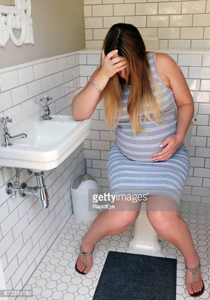 Very pregnant and miserable woman sitting on toilet seat, crying