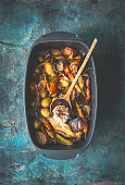Very rustic roasted vegetables stew or ragout with wild game and wild fowl and forest mushrooms in black backing dish with wooden cooking spoon on dark aged background, top view. Country food