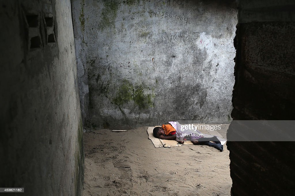 A very sick Saah Exco, 10, lies in a back alley of the West Point slum on August 19, 2014 in Monrovia, Liberia. The boy was one of the patients that was pulled out of a holding center for suspected Ebola patients when the facility was breached by protestors Friday night. A local clinic Tuesday refused to treat the boy, according to residents, because of the danger of infection. Saah's mother died of suspected but untested Ebola in West Point, and his brother, Tamba, 6, died on Friday in the holding center. The virus has killed more than 1,000 people in four African nations, more in Liberia than any other country.