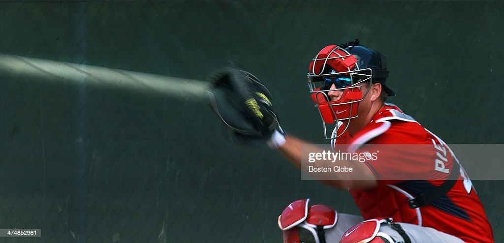 A very slow shutter speed on the camera creates the comet-like effect of the baseball, even showing the spinning seams, as it zooms into the mitt of Red Sox catcher A.J. Pierzynski as he works in the bullpen during Boston Red Sox spring training at JetBlue Park on Feb. 20, 2014.