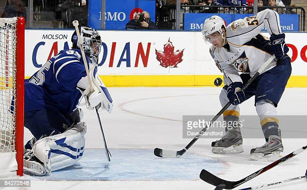 Vesa Toskala of the Toronto Maple Leafs keeps an eye on the puck as does Michael Santorelli of the Nahville Predators during their NHL game at the...