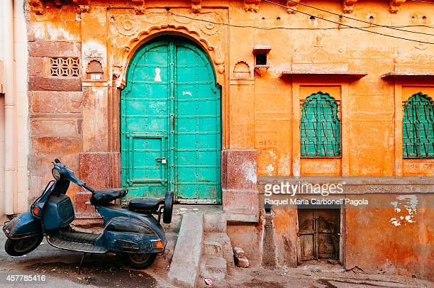 Vespa motorbike parked in front of a colorful haveli in the old city