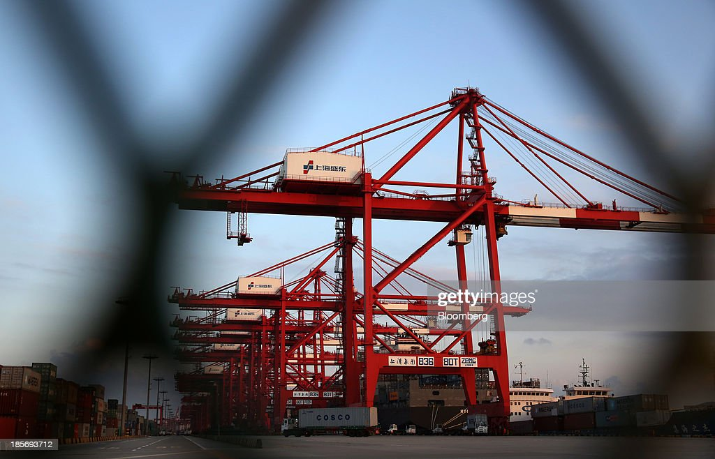 A vessel being loaded with shipping containers is seen through a fence at the Yangshan Deep Water Port, part of China (Shanghai) Pilot Free Trade Zone's Yangshan free trade port area, in Shanghai, China, on Wednesday, Oct. 23, 2013. The area is a testing ground for free-market policies that Premier Li Keqiang has signaled he may later implement more broadly in the world's second-largest economy. Photographer: Tomohiro Ohsumi/Bloomberg via Getty Images