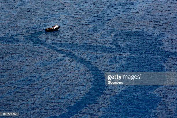 A vessel cuts through oil floating on the water's surface near the BP Plc Deepwater Horizon oil spill site in the Gulf of Mexico near the coast of...