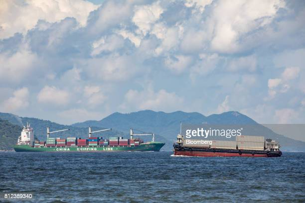 A vessel transporting shipping containers by Orient Overseas Container Line a unit of Orient Overseas International Ltd right sails past the CSCL Sao...