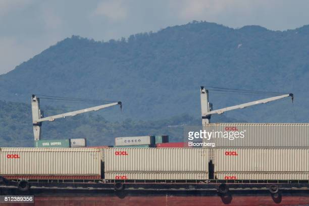 A vessel transporting shipping containers by Orient Overseas Container Line a unit of Orient Overseas International Ltd front sails past another ship...