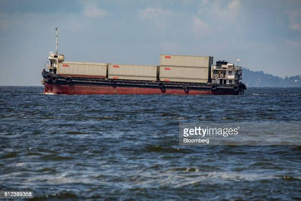 A vessel transporting shipping containers by Orient Overseas Container Line a unit of Orient Overseas International Ltd sails in Hong Kong China on...