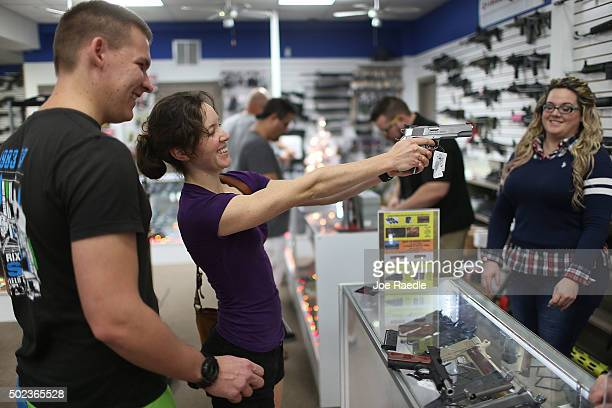 Vesta Parks checks out a handgun as she prepares to buy Tim Schneider one as a Christmas present at the National Armory gun store on December 23 2015...