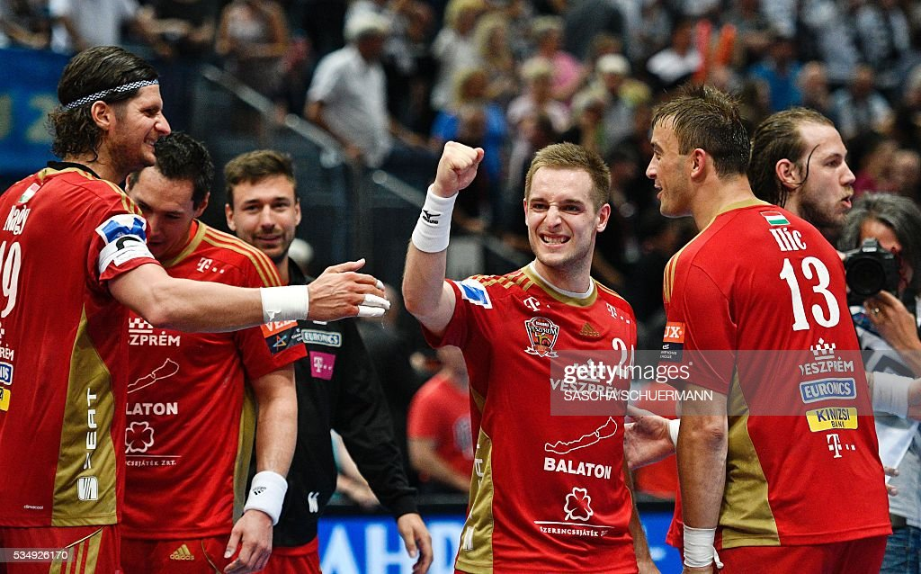 Veszprém's Laszlo Nagy (L-R) Gasper Marguc and Momir Ilic celebrate after the Handball EHF Champions League final Four semi-final match between THW Kiel and MVM Veszprem in Cologne, western Germany, on May 28, 2016. / AFP / SASCHA