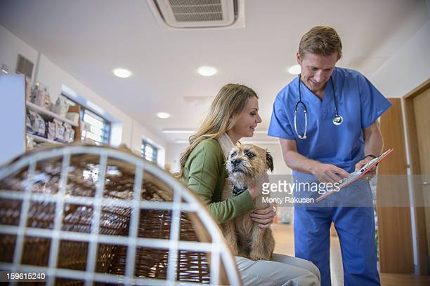 Vet talking to woman holding pet dog in veterinary waiting room