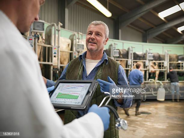 Vet with digital tablet and farmer in discussion in rotary milking parlour on dairy farm with cows