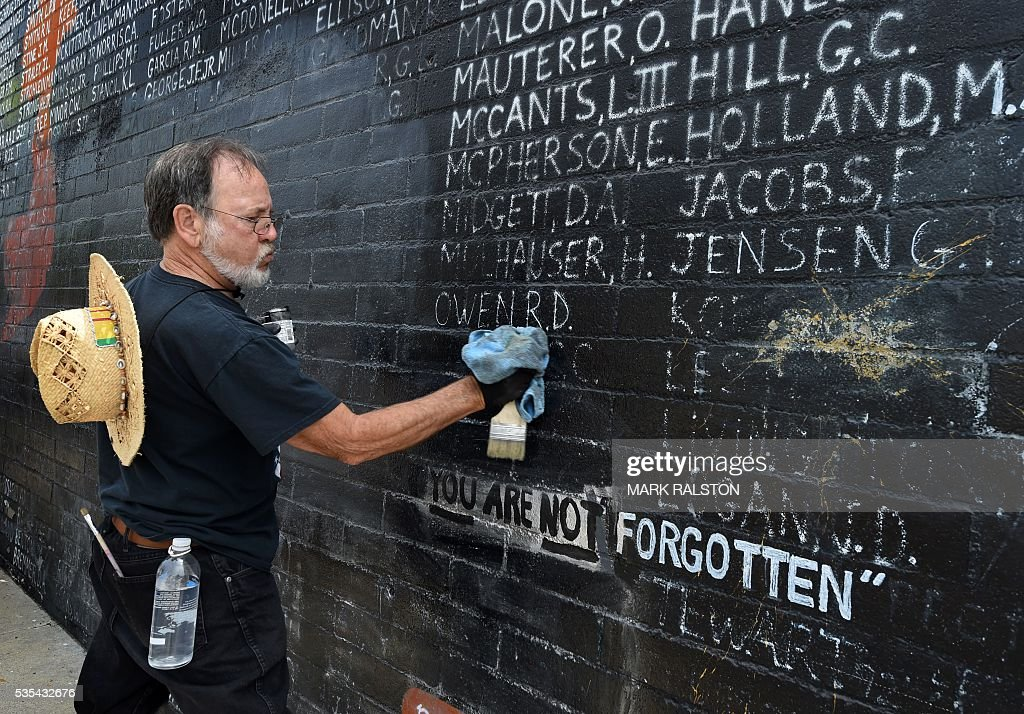 Veteran Charle Saulenas cleans a Veterans Memorial containing the names of 2,273 unaccounted and missing in action (MIA) Vietnam war soldiers after vandals covered the mural with silver paint graffiti prior to Memorial Day in Venice Beach, California on May 29, 2016. / AFP / Mark Ralston