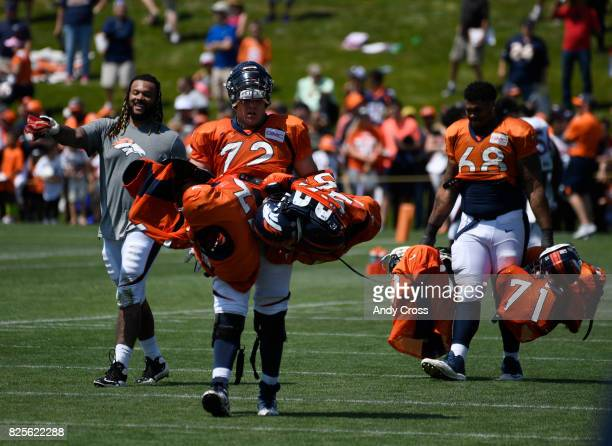 Veteran Denver Broncos offensive guard Billy Turner #77 left guides Denver Broncos rookie offensive tackle Garett Bolles and Denver Broncos rookie...