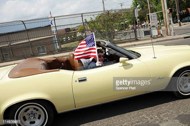 A veteran drives by in a convertible displaying an American flag during the Memorial Day Parade in the economically stressed region of the...