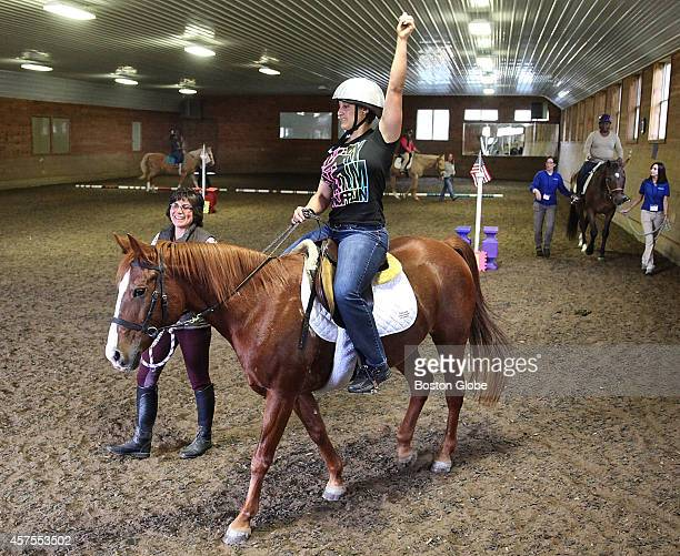 Veteran Elisa Long of PA rides 'Dream' around an indoor track at BINA Farm Center in Norfolk Mass on October 7 2014
