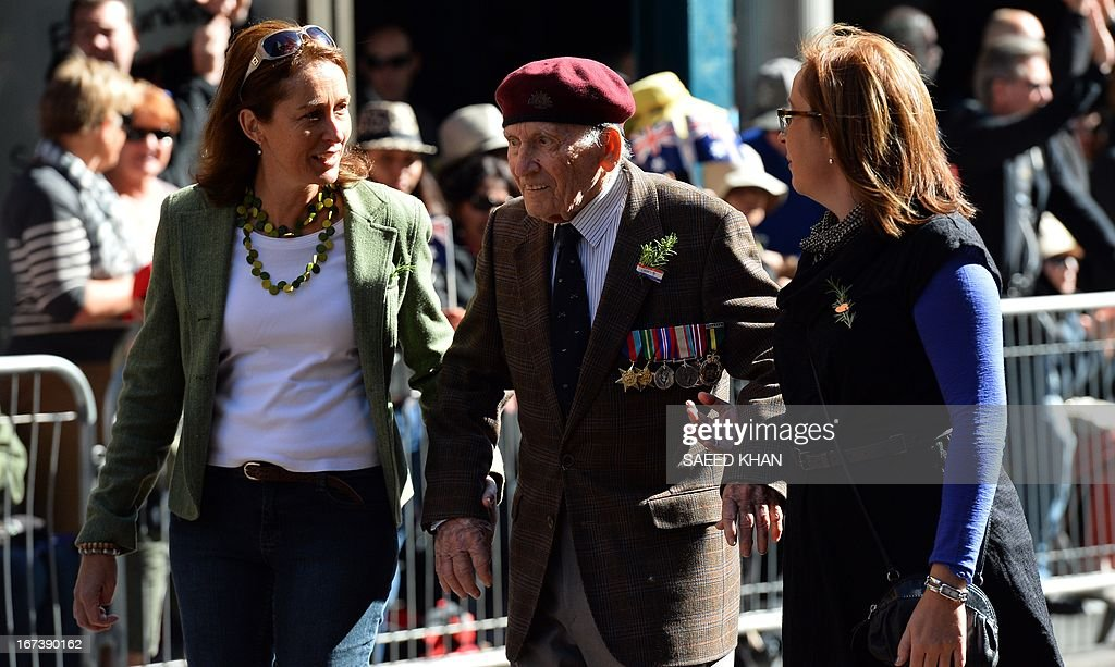 A veteran is given a helping hand as he participates in the Anzac Day march in Sydney on April 25, 2013. Tens of thousands of Australians and New Zealanders turned out on April 25 to honour their war dead, with moving tributes to fallen mates and calls not to forget those injured in conflict. AFP PHOTO / Saeed Khan