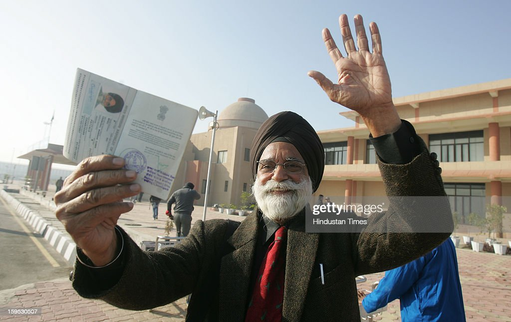 A veteran journalist and SAFMA member Chanchal Manohar Singh waves while showing his passport, as he availed the first opportunity to get Visa on Arrival by Pakistan, at India-Pakistan joint border checkpost Attari on January 15, 2013 near Amritsar, India. India has suspended the On Arrival Visa facility for Senior citizen at border soon after the inauguration amid tensions on the Line of Control (LoC) over the killing and mutilation of two Indian soldiers.
