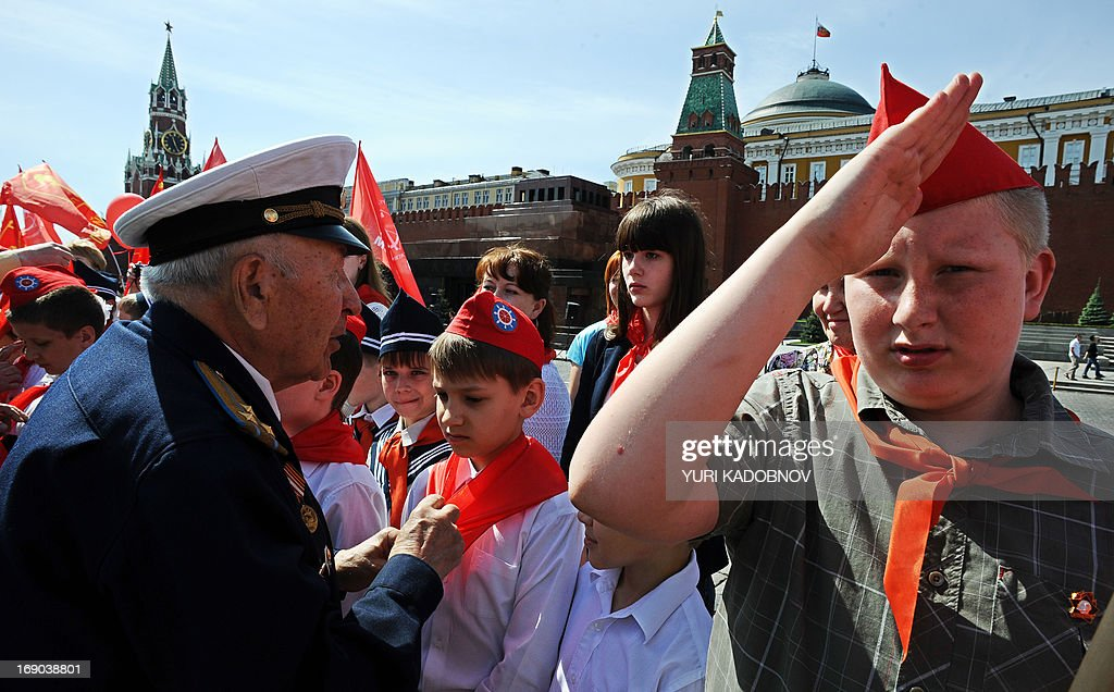 A veteran of the Soviet Army and Russian Communist Party (L) ties red scarves around childrens' necks, symbolizing their initiation into the Young Pioneer Youth communist group, created in the Soviet Union for children 10-14 years old, in Moscow's Red square on May 19, 2013 during the organization's celebration day. Some three thousands pioneers took part in the ceremony.