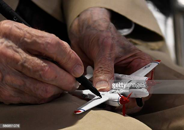 WWII Veteran P38 pilot Frederic Arnold autographs a model P38 airplane for Greyson Mezo at the Arnold's Lest We Forget The Mission statue unveiling...