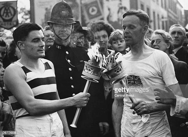 Veteran runner H J Bignall hands over the Olympic torch to Fred Prevett at Redhill Surrey during the flame's journey from Dover to Wembley Stadium...