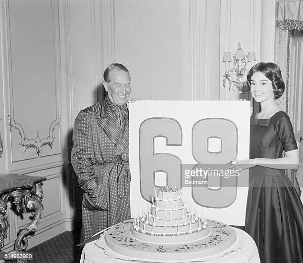 Veteran screen and stage star Maurice Chevalier gets some assistance from his charming costar Audrey Hepburn in celebrating his 68th birthday on the...