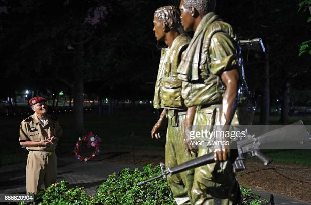 A veteran stands before statues at the Vietnam Veterans Memorial during a candlelight vigil in Washington DC on May 26 prior the Rolling Thunder...
