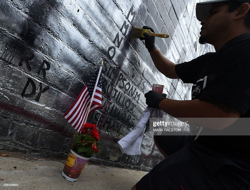 Veterans and community members help cleanup a Veterans Memorial containing the names of 2,273 unaccounted and missing in action (MIA) Vietnam war soldiers after vandals covered the mural with silver paint graffiti prior to Memorial Day in Venice Beach, California on May 29, 2016. / AFP / Mark Ralston