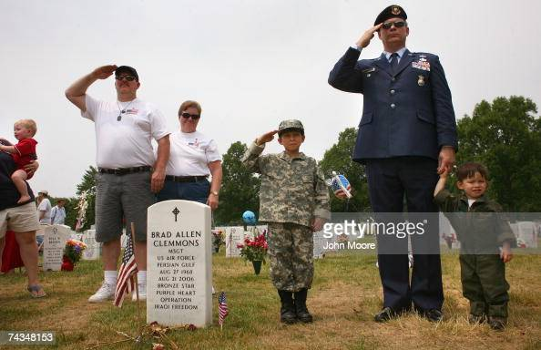 Veterans and family members of slain American soldiers pay their respects during the playing of 'Amazing Grace' in 'Section 60' of the Arlington...