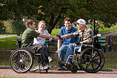 Two war veterans with spinal cord injury in wheelchairs shaking hands with their friends in a park
