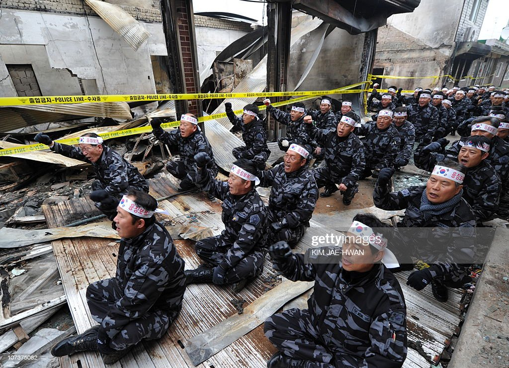 Veterans of a South Korean commando unit chants the words 'revenge and punishment' amongst the rubble of bomb affected buildings, during a rally in Yeonpyeong island on December 1, 2010. The US and South Korean navies on December 1, ended a major exercise intended to warn North Korea and announced more drills, but world powers remained divided over how to deal with the nuclear-armed regime.