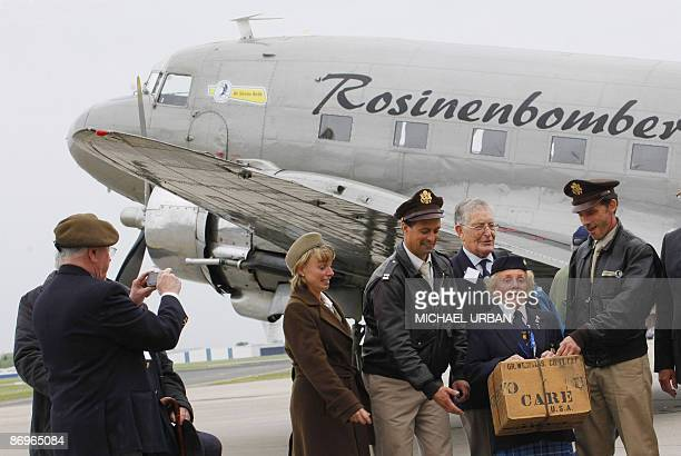 Veterans of the Berlin airlift pose in front of a vintage Douglas DC3 aircraft known as a 'Rosinenbomber' at the airport of Schoenefeld near Berlin...