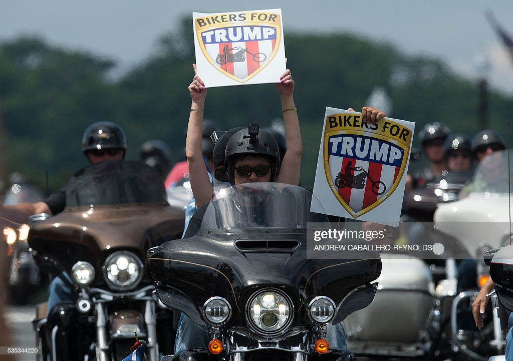 Veterans ride on motorbikes holding signs of support for Republican presidential candidate Donald Trump during the Rolling Thunder rally in Washington, DC on May 29, 2016. Rolling Thunder is an advocacy group dedicated to raising awareness for American Prisoners of War and warriors currently missing in action. / AFP / andrew caballero-reynolds